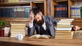Man in classic suit, professor with concentrated busy face. Sits in library near piles of books, bookshelves on background, defocused. Man or bearded teacher stock photos