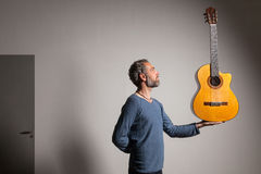 Man with classical guitar. Portrait of man grizzled with classical guitar, wall background Stock Photos