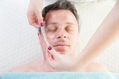 Man with clay facial mask in beauty spa Royalty Free Stock Photography