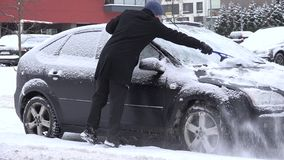 Man clean car snowy window with brush in winter time. 4K stock video footage