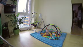Man clean floor with hoover and curious baby on play mat. 4K stock video footage