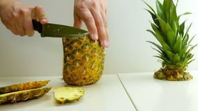 Man clean pineapple on white backgroun with knife stock video footage