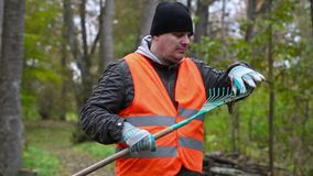 Man clean rake from the leaves in the park stock footage