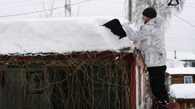 Man clean the roof from the snow. Large white snowdrifts on the roof are thrown off by a man with a plastic shovel stock video footage