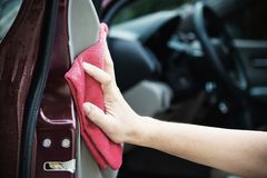 Man clean and wax the car. Outdoor car maintenance service concept stock photo