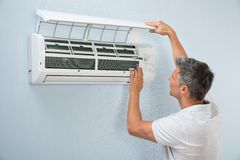 Man cleaning air conditioning system. Portrait Of A Man Cleaning Air Conditioning System Royalty Free Stock Image