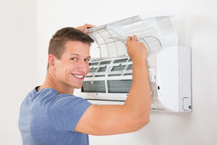 Man Cleaning Air Conditioning System. Young Happy Man Cleaning Air Conditioning System At Home Stock Image
