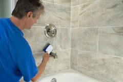 Man cleaning bathtub tiles and fixtures with scrub brush Stock Images