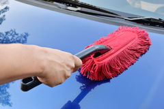 Man cleaning a blue car,. With the use of wood dust car Stock Image