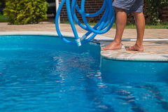 Man cleaning the blue swimming pool with hose, closeup. Man cleaning the swimming pool with blue hose, service, closeup Royalty Free Stock Images