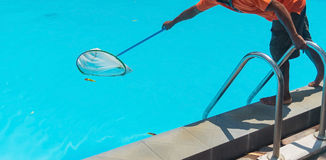 Man cleaning the blue swimming pool from leaves with cleaning ne Royalty Free Stock Images