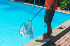 Man cleaning the blue swimming pool from leaves with cleaning ne Stock Photography