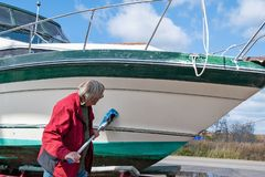 Man cleaning boat hull royalty free stock photography