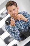 Man cleaning camera lens with brush Stock Images