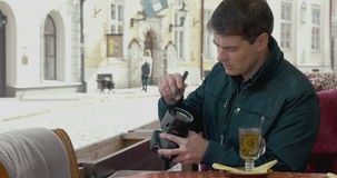 Man cleaning camera lens in outdoor cafe stock video