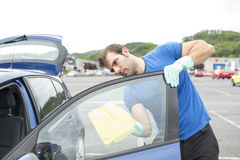 Man cleaning car glass with sponge. Stock Image