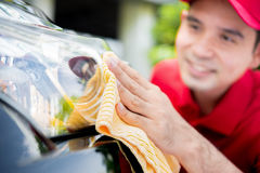 A man cleaning car headlight Royalty Free Stock Photo