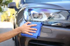 Man cleaning car headlight with rag. Outdoors Royalty Free Stock Photo
