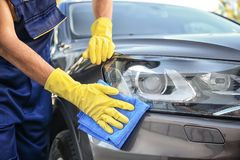 Man cleaning car headlight with rag. Outdoors Stock Photo