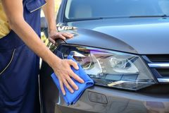 Man cleaning car headlight with rag. Outdoors Royalty Free Stock Image