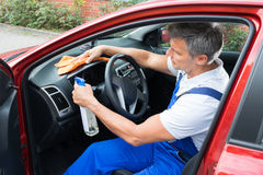 Man Cleaning Car Interior. Mature man cleaning car interior Stock Photo