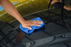 Car Wipes. Man cleaning car with microfiber Stock Image