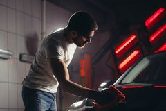 Man cleaning car with microfiber cloth, car detailing or valeting concept. A man cleaning car with microfiber cloth, car detailing or valeting concept. Selective royalty free stock images