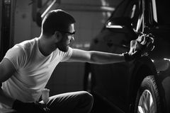 Man cleaning car with microfiber cloth, car detailing or valeting concept. A man cleaning car with microfiber cloth, car detailing or valeting concept. Selective stock photography