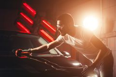 Man cleaning car with microfiber cloth, car detailing or valeting concept. A man cleaning car with microfiber cloth, car detailing or valeting concept. Selective stock photo
