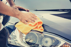 A man cleaning car with microfiber cloth Stock Image