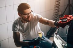 Man cleaning car with microfiber cloth, car detailing or valeting concept. A man cleaning car with microfiber cloth, car detailing or valeting concept. Selective stock image