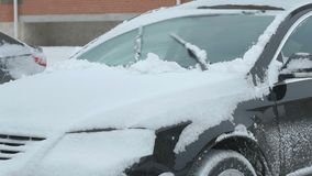 Man cleaning car from snow. Caucasian man is cleaning black car from snow during snowfall in the yard stock footage