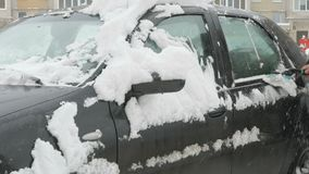Man cleaning car from snow. Caucasian man is cleaning black car from snow during snowfall in the yard stock video footage
