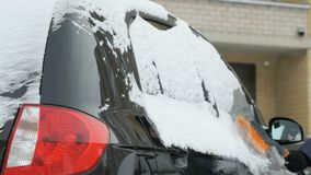 Man cleaning car from snow. Caucasian man in casual clothes cleaning car from the snow near the house in winter against the backdrop of multi-storey residential stock video footage
