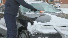 Man cleaning car from snow. Caucasian man in casual clothes cleaning car from the snow near the house in winter against the backdrop of multi-storey residential stock video