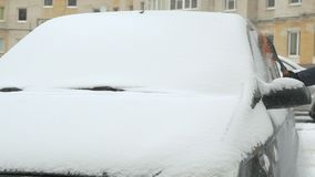 Man cleaning car from snow. Caucasian man in casual clothes cleaning car from the snow near the house in winter against the backdrop of multi-storey residential stock footage