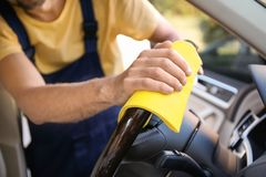 Man cleaning car steering wheel with rag. Closeup royalty free stock images