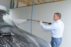 Man cleaning car using spray water Stock Image