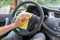 Man is cleaning car wheel and dashboard with microfiber cloth.  Stock Images