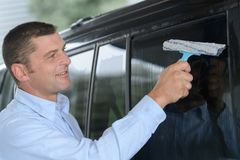 Man cleaning car window Stock Photography