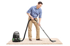 Man cleaning a carpet with a vacuum cleaner Royalty Free Stock Photography