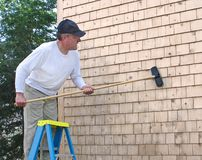 Man cleaning cedar shingles. From ladder Stock Photo