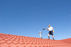 Man cleaning chimney on tiled roof Royalty Free Stock Photo
