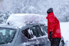 Man is cleaning clean off his car of snow cover by brush. Snow covered car. Heavy Snow Cleaning Car under snow heavy snowfall. Young Man is cleaning clean off stock photos