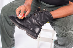 Man cleaning combat shoes Royalty Free Stock Images