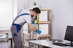 Man Cleaning Desk In Office. Close-up Of A Young Man Cleaning Desk In Office stock photos