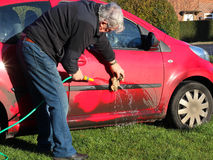 Man cleaning a dirty car. An elderly man cleaning a dirty motor vehicle with a hose pipe and a cloth Stock Photo