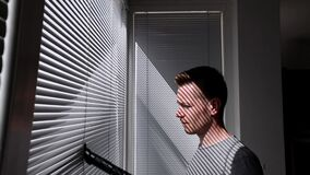 Man cleaning dust from window blind by vacuum cleaner at home