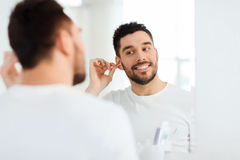 Man cleaning ear with cotton swab at bathroom Stock Photos