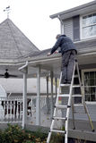 Man cleaning Eaves troughs. A homeowner tackles the chore of cleaning out the eaves troughs during late fall Royalty Free Stock Photography